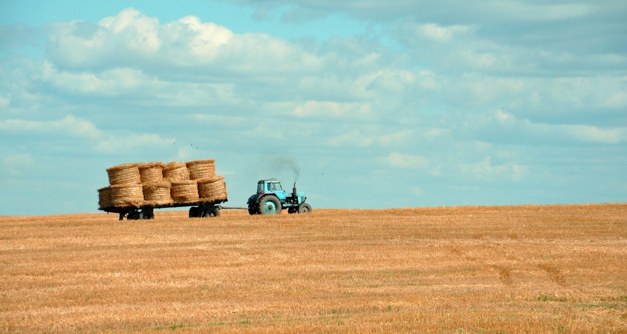 tractor in field towing bales of hay